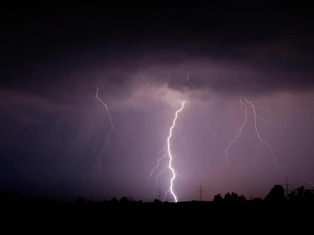 A photo of lightning striking the ground against a moody purple sky