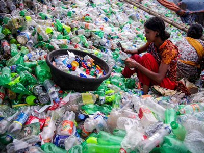 A worker sorts plastic in a recycling plant in Bangladesh. A new bacteria could make her job obsolete