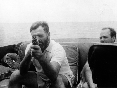 Hemingway led a life of adventure and, sometimes, violence. The author is shown here holding a tommy gun aboard the Pilar in 1935.