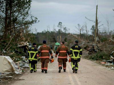 First responders walk through a neighborhood in Beauregard, Alabama.