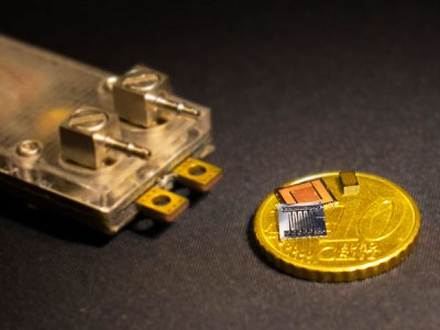 Picture of the top and bottom sides of the chips with integrated microfluidic cooling, next to the miniaturized power converter