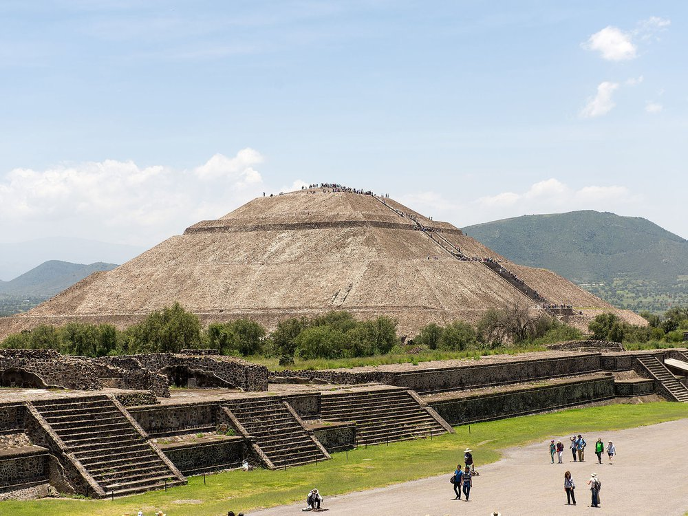 A view of the Pyramid of the Sun at Teotihuacan, a huge pyramid that stands several stories tall over an expansive avenue populated by tourists