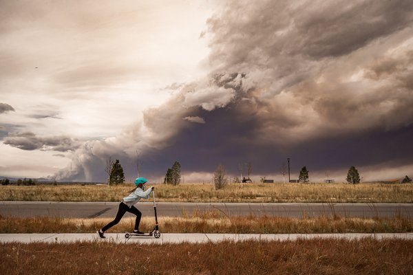 Riding a scooter while wildfires rage behind her thumbnail