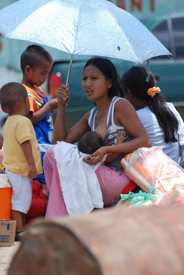 A young woman giving eat to her little boy at Samariapo Port thumbnail
