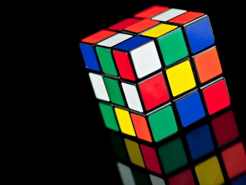 Rubik's Cube toy on black background with reflection.