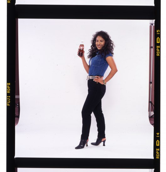 Selena in a blue vest and black pants holding a bottle of Coca-Cola