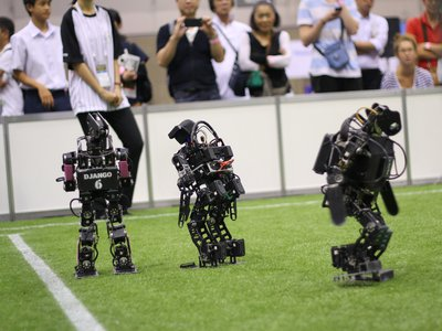 """Robots in the """"kid-size"""" (really around 16 inches tall) Robocup soccer league face off. These """"Rhoban"""" bots, built by students at the University of Bordeaux, took first place in their division in the 2017 competition."""