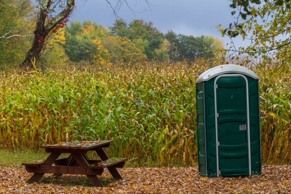 An outhouse next to a picnic table by a cornfield thumbnail