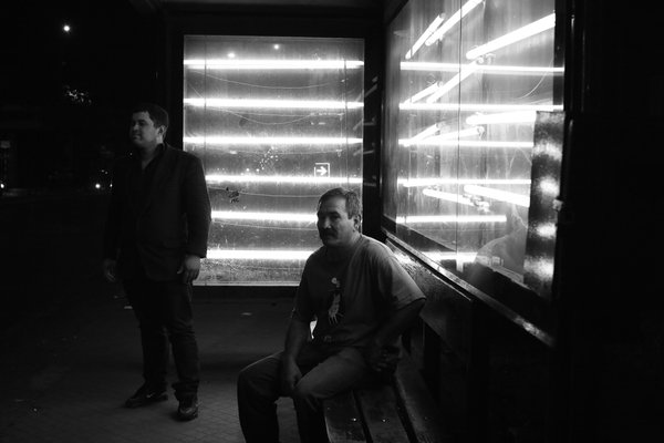 Men at a bus stop at night in Asuncion, Paraguay thumbnail
