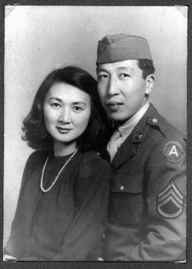 Black and white image of newlywed couple with man in army uniform