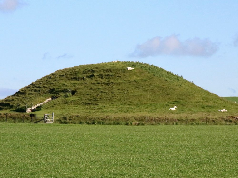 A large grassy mound with an entrance cut into the side, underneath a blue sky