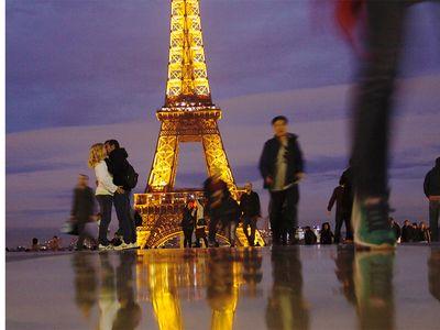 A couple kisses near the Eiffel Tower.