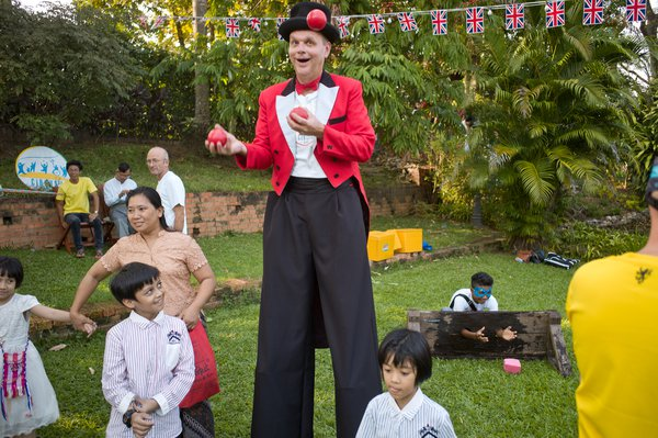 Clown juggling during British Day party, Myanmar thumbnail