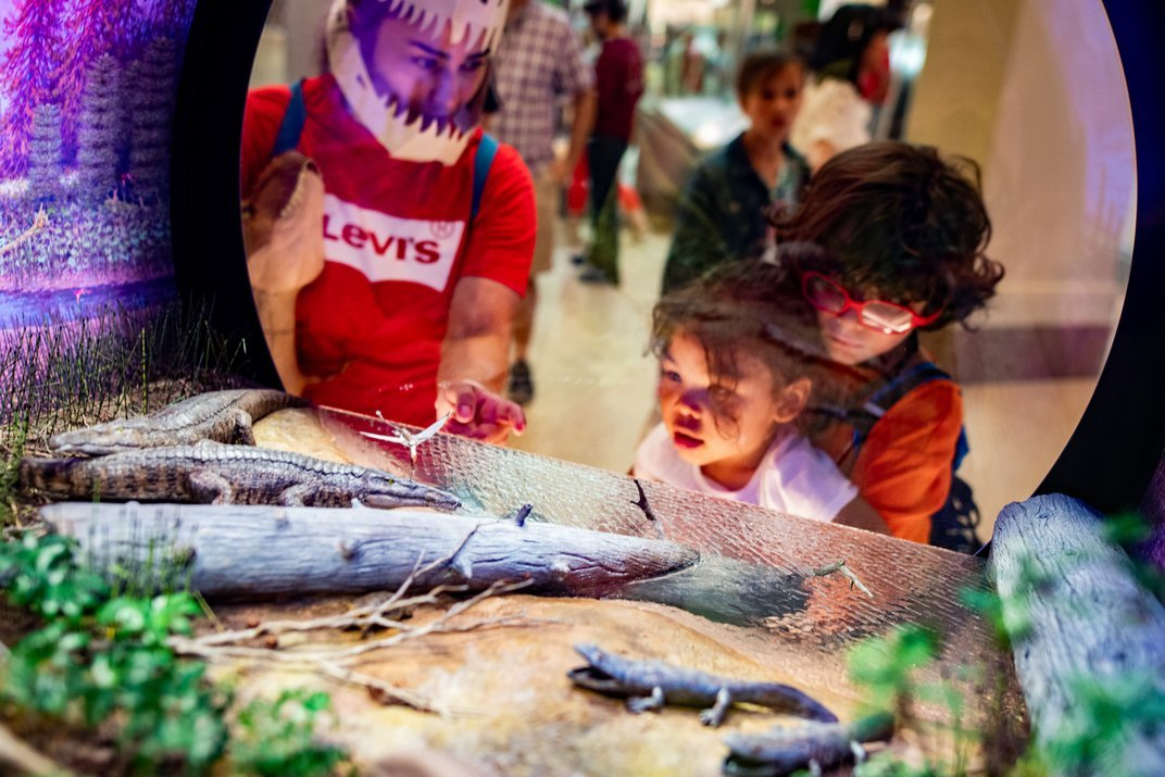 Three children look at a colorful recreation of an extinct ecosystem from 219-209 million years ago.