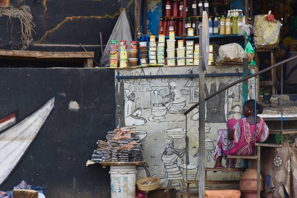 A store keeper sits by her shop in downtown Dakar thumbnail