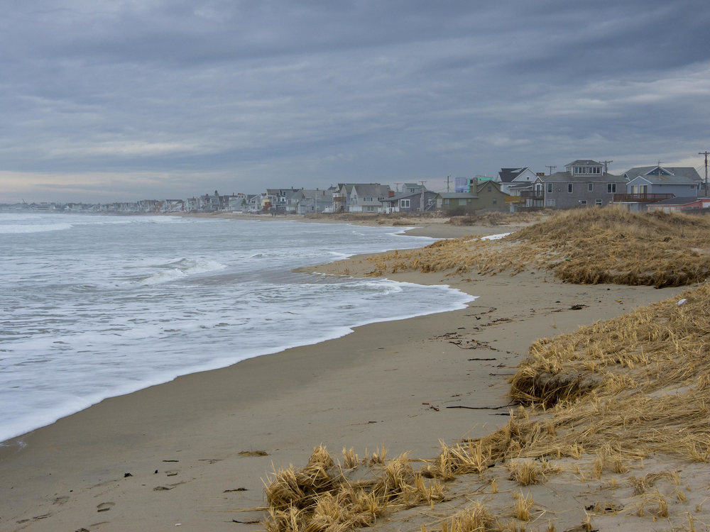 A photograph shows Wells Beach in southern Maine with beach houses on the horizon