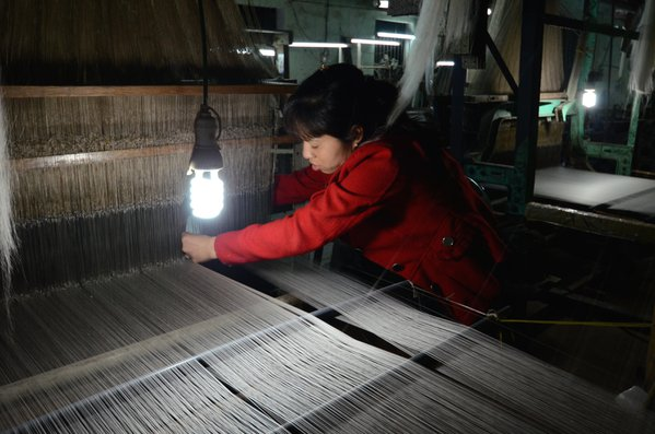 A woman loads a silk weaving loom thumbnail