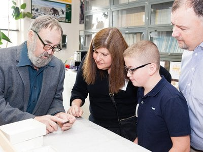 Ten-year-old Noah Cordle visited the National Museum of Natural History on November 3 to donate a Clovis point he found in New Jersey. He and his parents (right) met with the museum's Dennis Stanford (left).