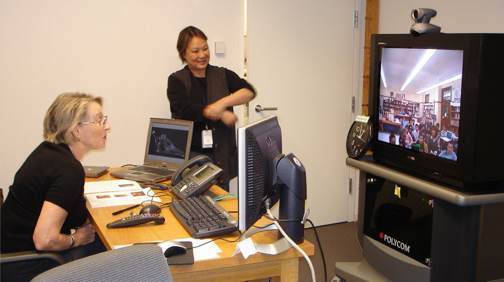 Image of two women looking at tv screen conducting a distance learning class