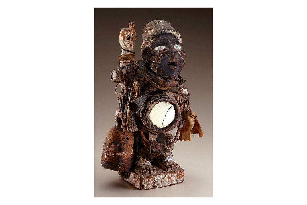 Ceramic or wooden sculpture of a person in a bowler hat, carrying some kind of instrument. Its abdomen appears hollowed out and lit from within.
