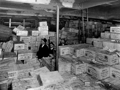 """Aboard the Coast Guard Cutter USS Seneca, Prohibition agents stand amidst cases of scotch whiskey confiscated from a """"rum runner"""" boat."""