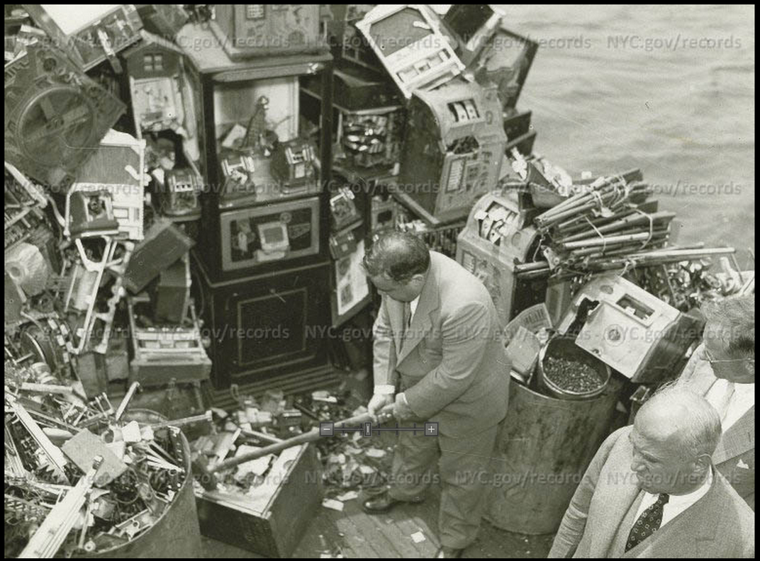 Mayor LaGuardia smashes a slot machine, as part of his attempt to destroy the slot machine racket, 1934.