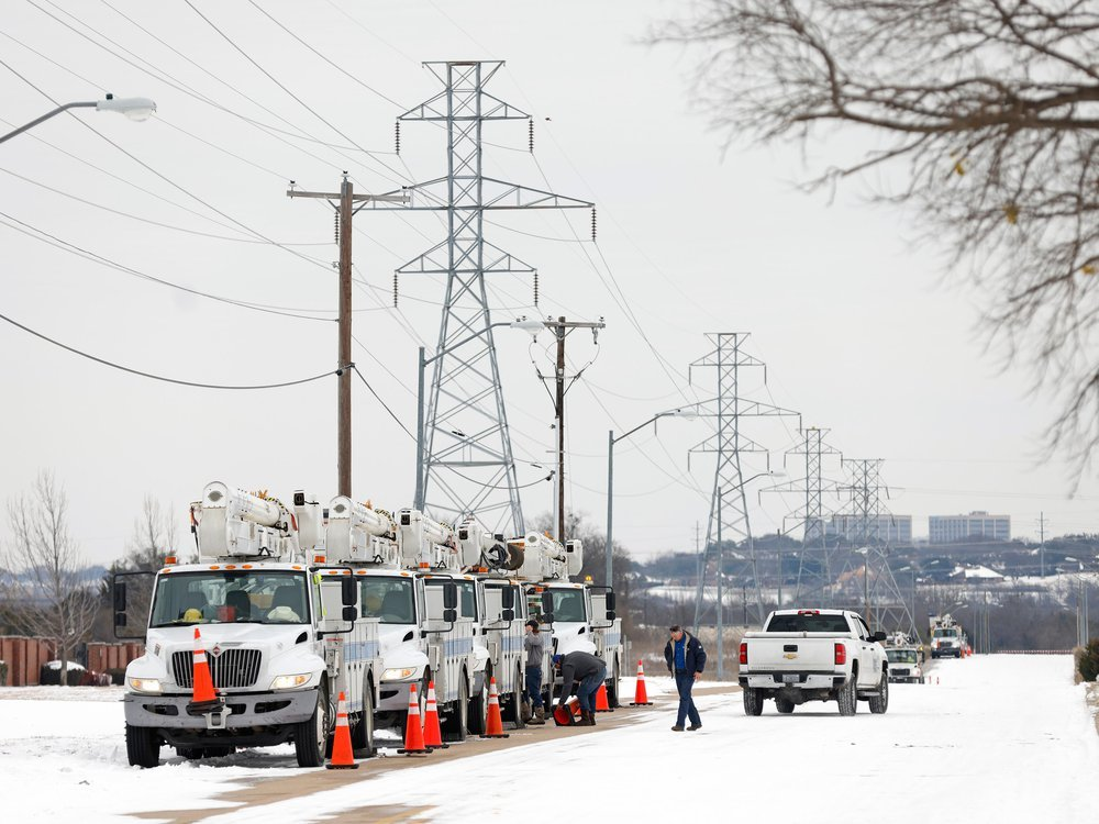 Trucks in a line under utility poles, parked on a snowy street
