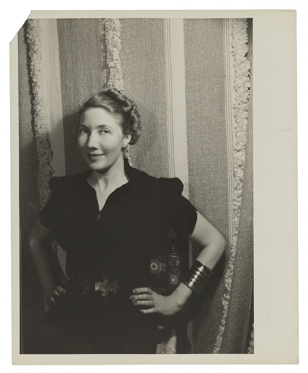 Woman in dark colored dress wearing a large cuff bracelet, photographed against one of her textile designs, which consists of various colors and textures in thick stripes.
