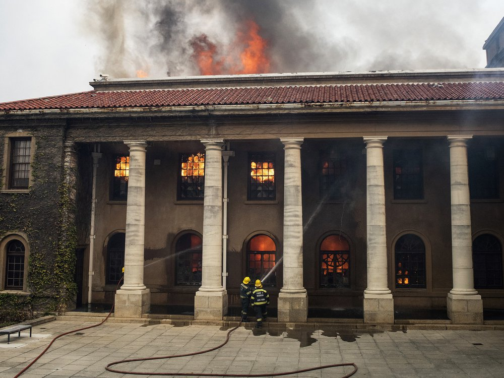 Two firefighters in gear, looking small compared to tall white columns, aim jets of water at the windows of a historic building; orange flames leap from the windows and ceiling of the structure and smoke pours out its top