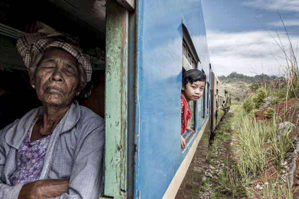 Girl looking out the window of a slow train and old woman sleeping, Myanmar, Asia thumbnail