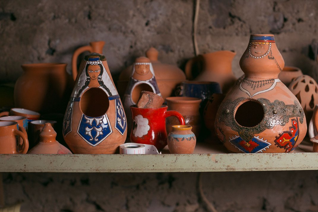 A selection of a few terracotta jars are glazed to appear as if wearing traditional Armenian dress.