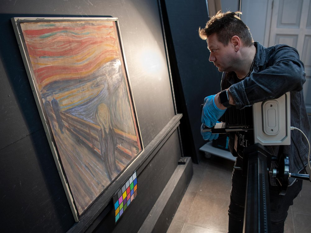 A white man in a blue shirt and gloves holds a camera in front of the canvas, which is about as tall as his torso