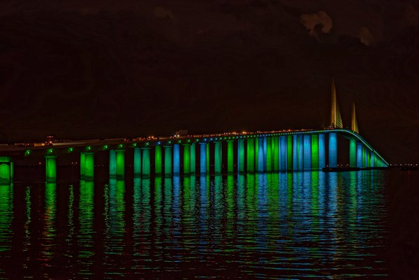 Green and blue light display illuminates Sunshine Skyway Bridge with reflection thumbnail