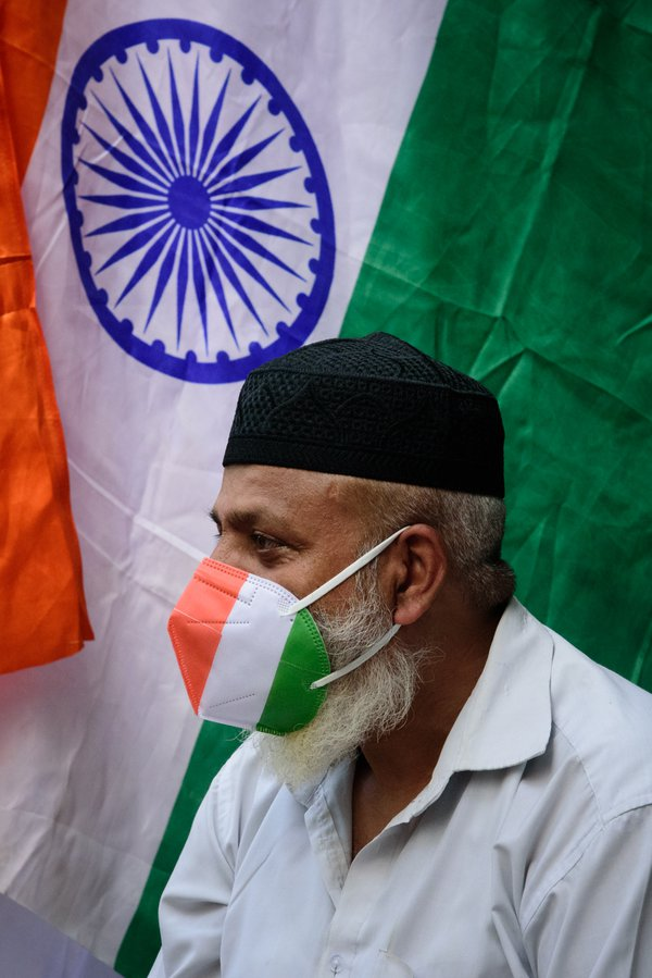 A man with mask painted with Indian flag's tricolor thumbnail