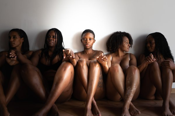 A young, black lady stares into the camera while holding hands with her friends. thumbnail