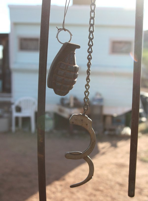 WWII-era hand grenade and a pair of handcuffs on display outside Rattlesnake Ranch, a Southeastern Arizona novelty shop. thumbnail