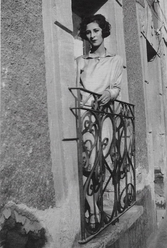 A black and white image of a woman leaning out a window