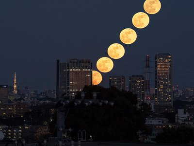 A compound image captures the rising moon over the Futako-Tamagawa Rise complex in Tokyo, Japan.