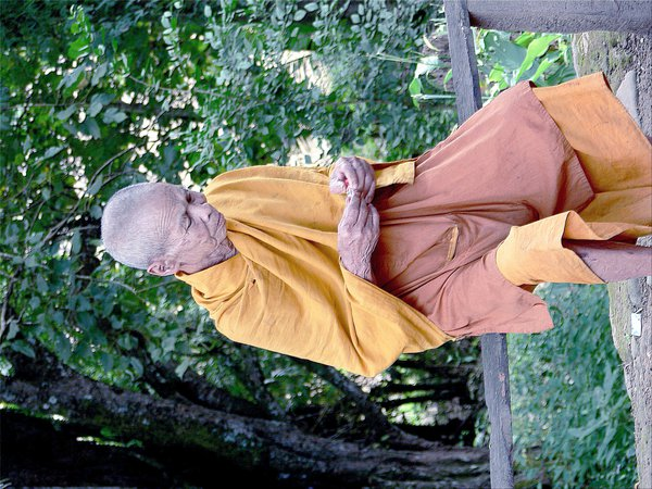 Laotian Buddhist monk opening a candy wrapper thumbnail