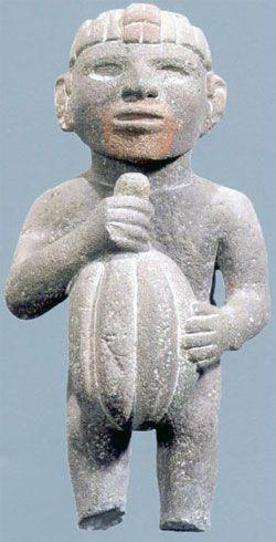 An Aztec figurine holds a cacao pod