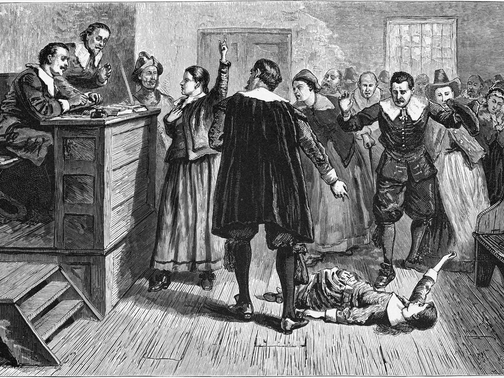 A black and white engraving of a courtroom scene; one woman stands in the center and raises a hand as though defending herself, while a young girl falls on the floor beneath a crowd of people