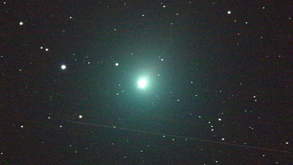 A photo of Comet 46P/Wirtanen. In the middle of the image is a ball of light that is glowing bright green against a starry black sky.