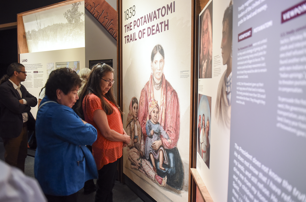 A young man and two women read exhibition text with the title 1838 Potawatomi Trail of Tears. The panel is illustrated with reproductions of drawings and paintings of 19th-century Potawatomi leaders.