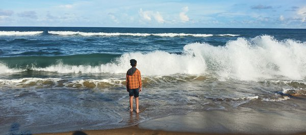 A boy admiring the frisky waves thumbnail