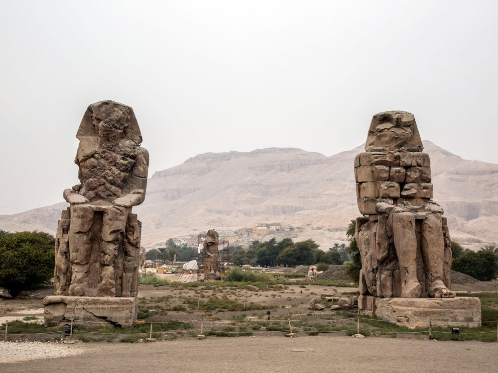 Statue of Memnon in the westbank in Luxor and in the background gurna of Maraai