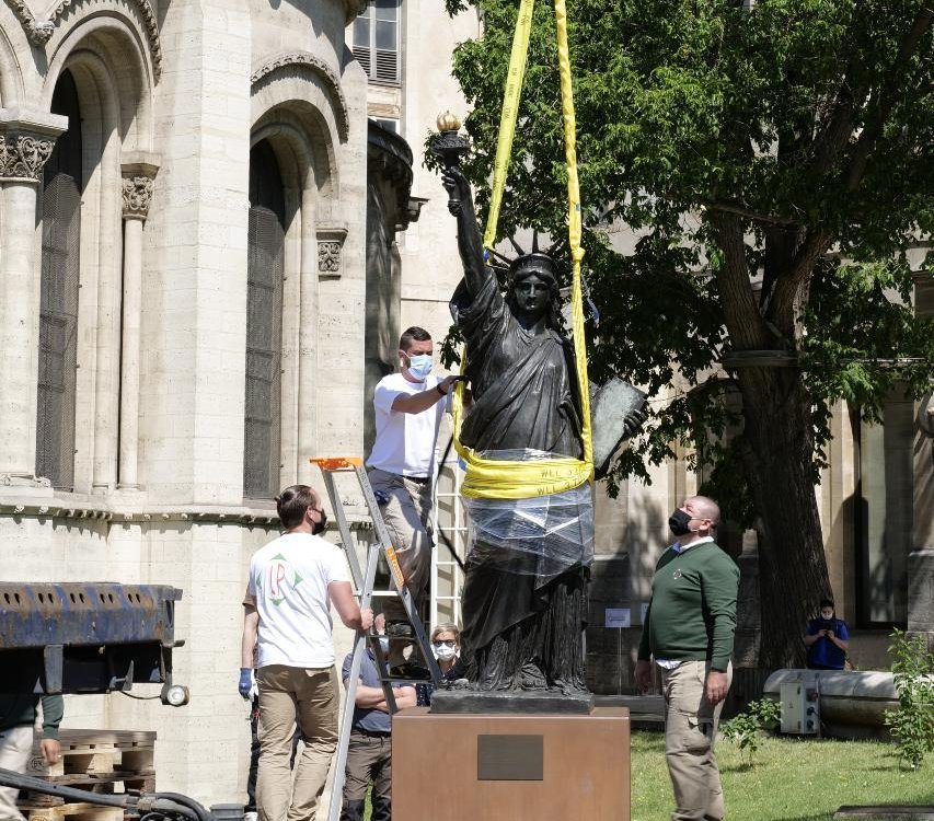 Workers remove a Statue of Liberty replica from its plinth