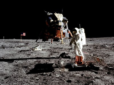 Apollo 11 astronaut Buzz Aldrin works at the deployed Passive Seismic Experiment Package on July 20, 1969. To the left of the United States flag in the background is the lunar surface television camera.