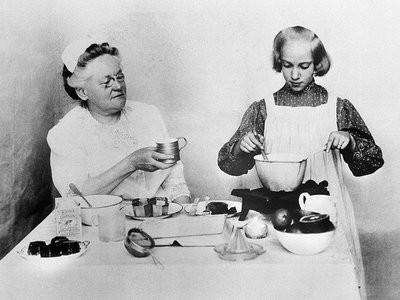 Fannie Farmer oversees one of her students, Martha Hayes Ludden, at the Boston Cooking School in 1900.