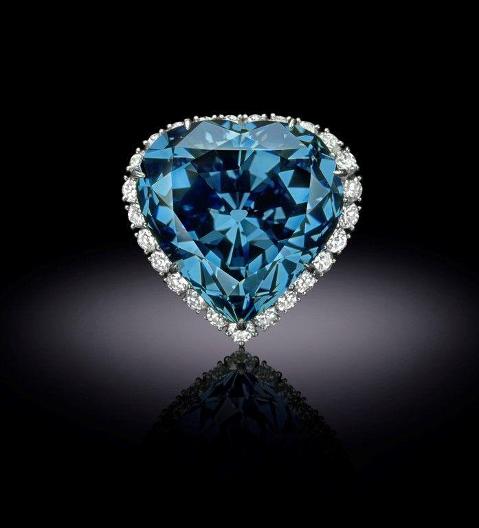 A blue, heart shaped diamond on a dark background.
