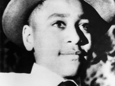 A young Emmett Till wearing a hat.